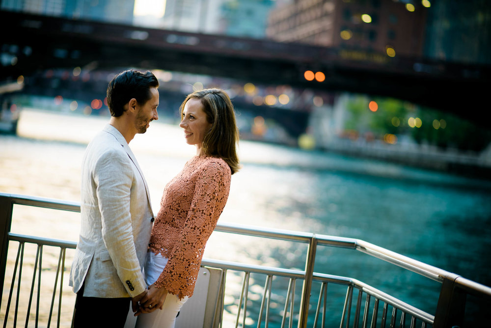 Couple embraces on the Chicago Riverwalk during their engagement session.