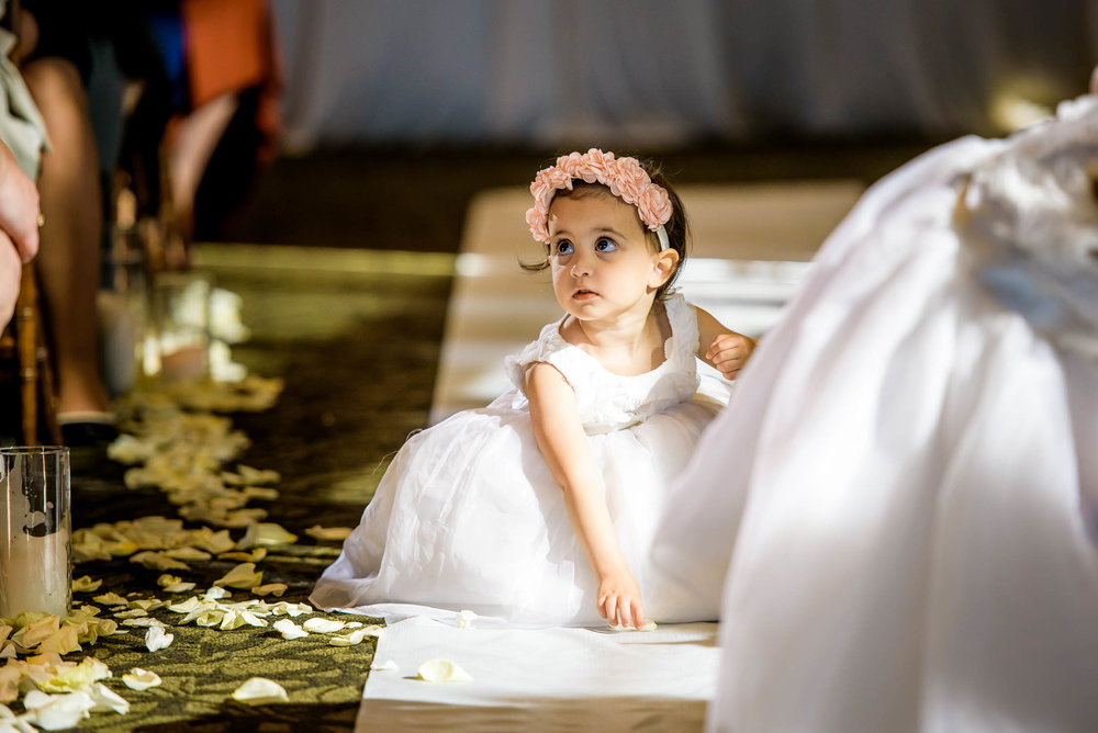 Flower girl picks up petals during a wedding at Independence Grove in Libertyville.