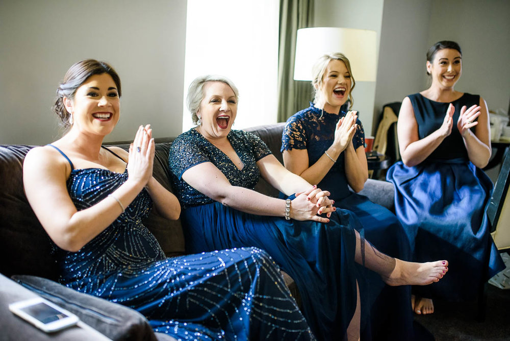 Bridesmaids react to seeing the bride at the Waldorf Astoria during her MCA Chicago winter wedding.