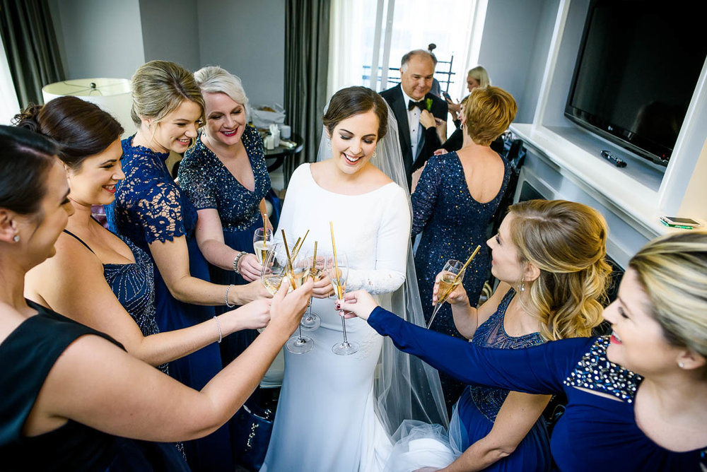 Bride and bridesmaids toast at the Waldorf Astoria during a MCA Chicago winter wedding.