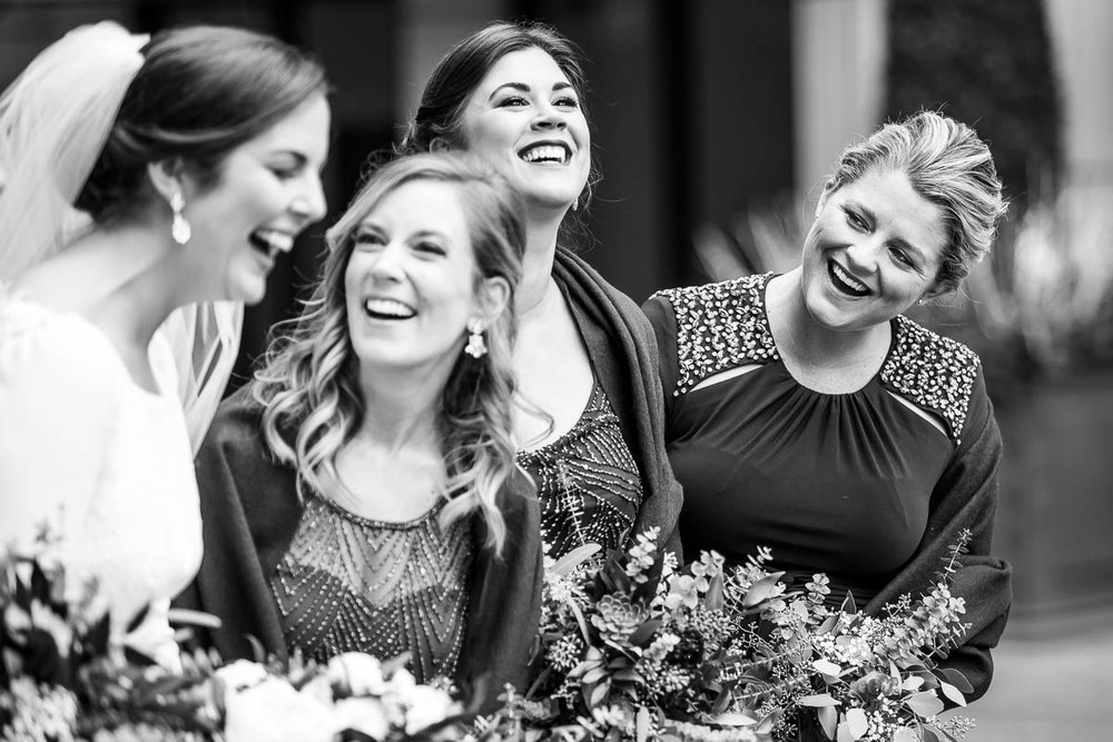 Bridesmaids share a moment and a laugh outside the Waldorf Astoria during a MCA Chicago winter wedding.