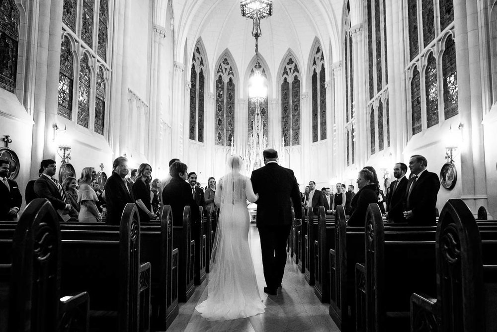 Father walks his daughter down the aisle during her winter Chicago wedding at St. James Chapel.