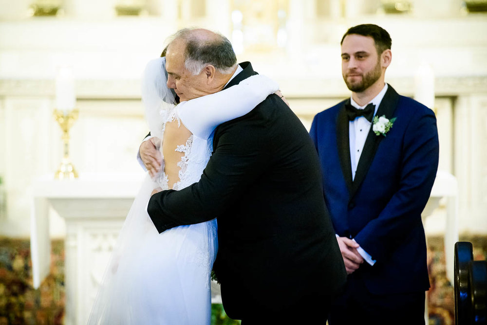 Father embraces his daughter during her St. James Chapel winter Chicago wedding.