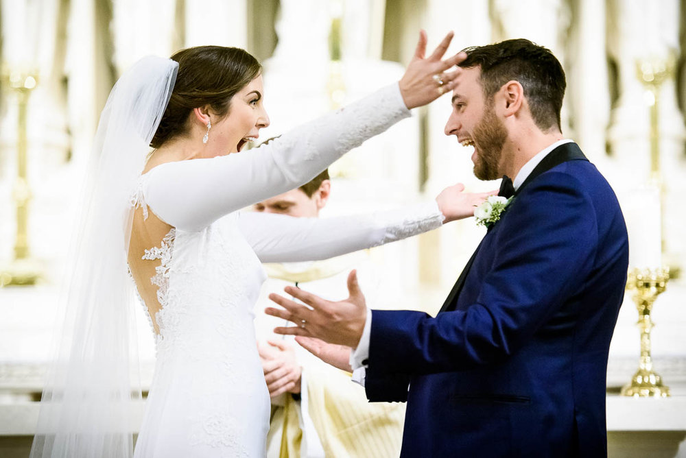Couple share a moment of excitement during their wedding ceremony at St. James Chapel.