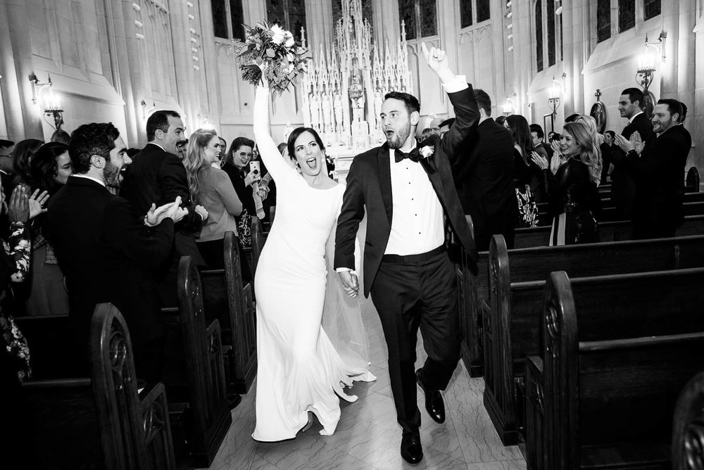 Bride & groom celebrate as they walk down the aisle after their St. James Chapel Chicago wedding ceremony.