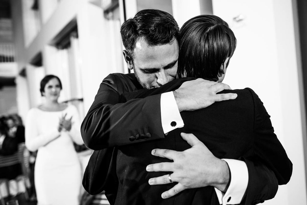 Groom and best man hug after his speech during a  winter wedding at the MCA Chicago.