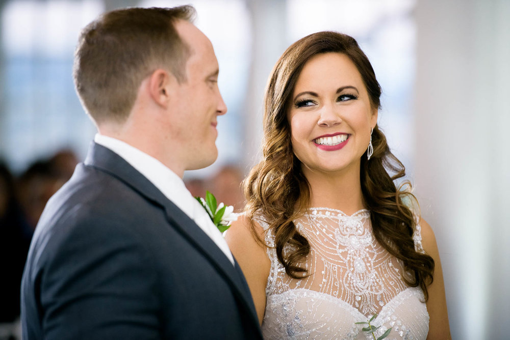 Bride and groom laugh together during their wedding ceremony at the Manor House in Littleton, Colorado.