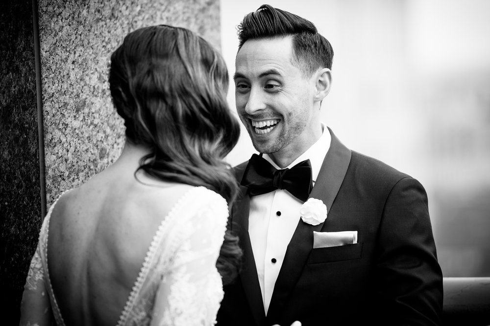 Groom reacts to seeing his bride before their Thompson Chicago wedding.  First look wedding photo.
