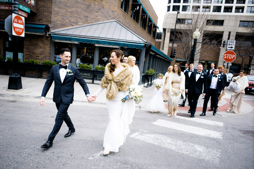 Bride and groom cross the street in the Gold Coast with their wedding party before their Thompson Chicago wedding.