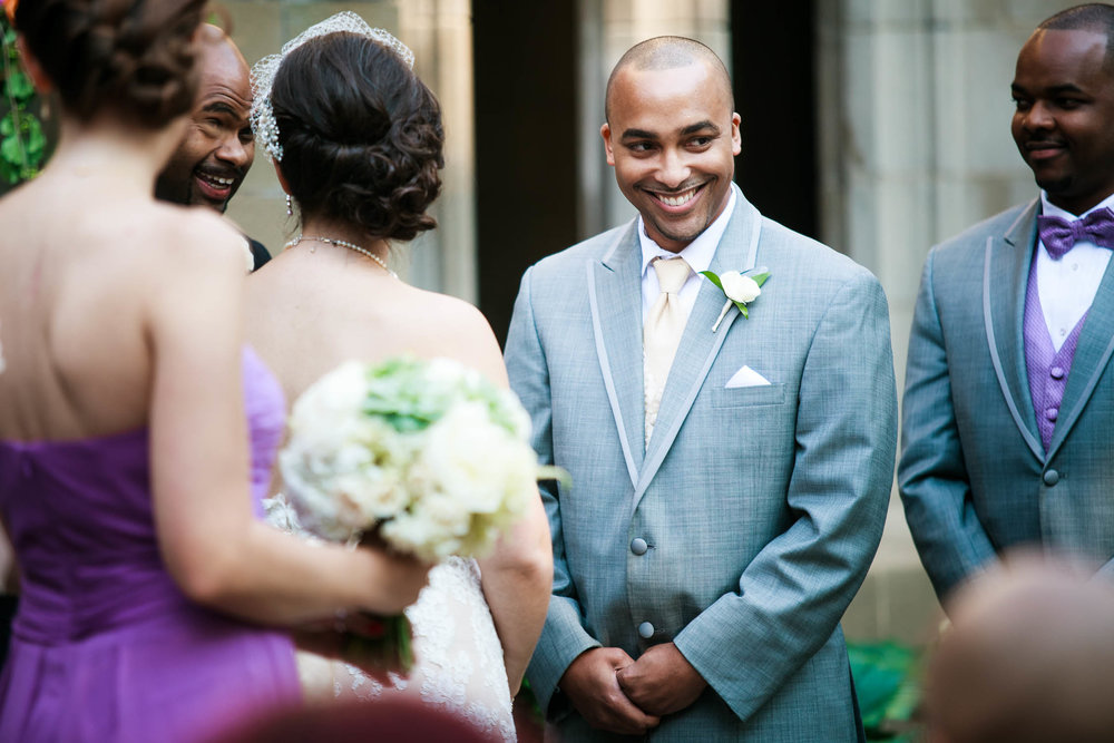 Groom cracks a smile during his wedding ceremony at the University of Chicago.