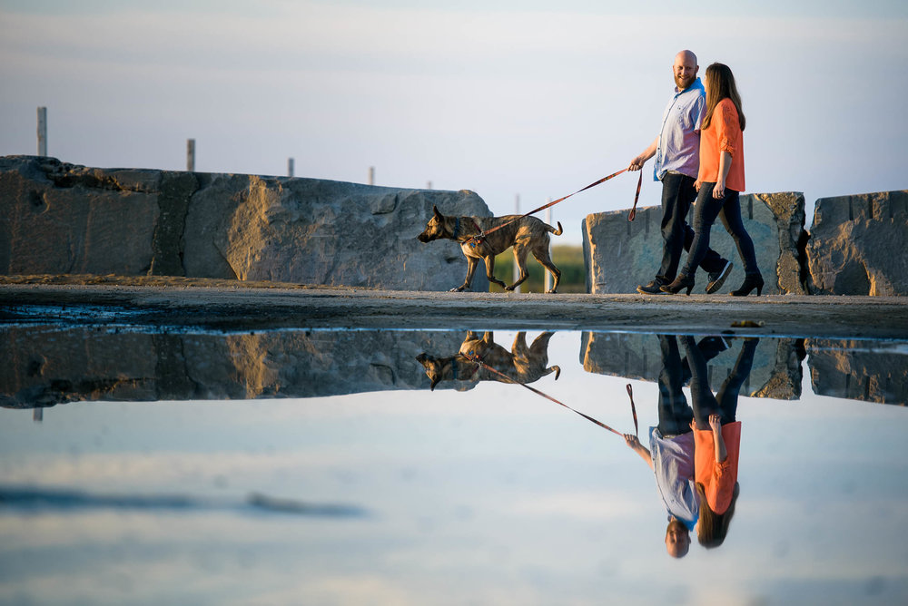 Couple walks with their dog at Montrose Beach in Chicago for their engagement session.