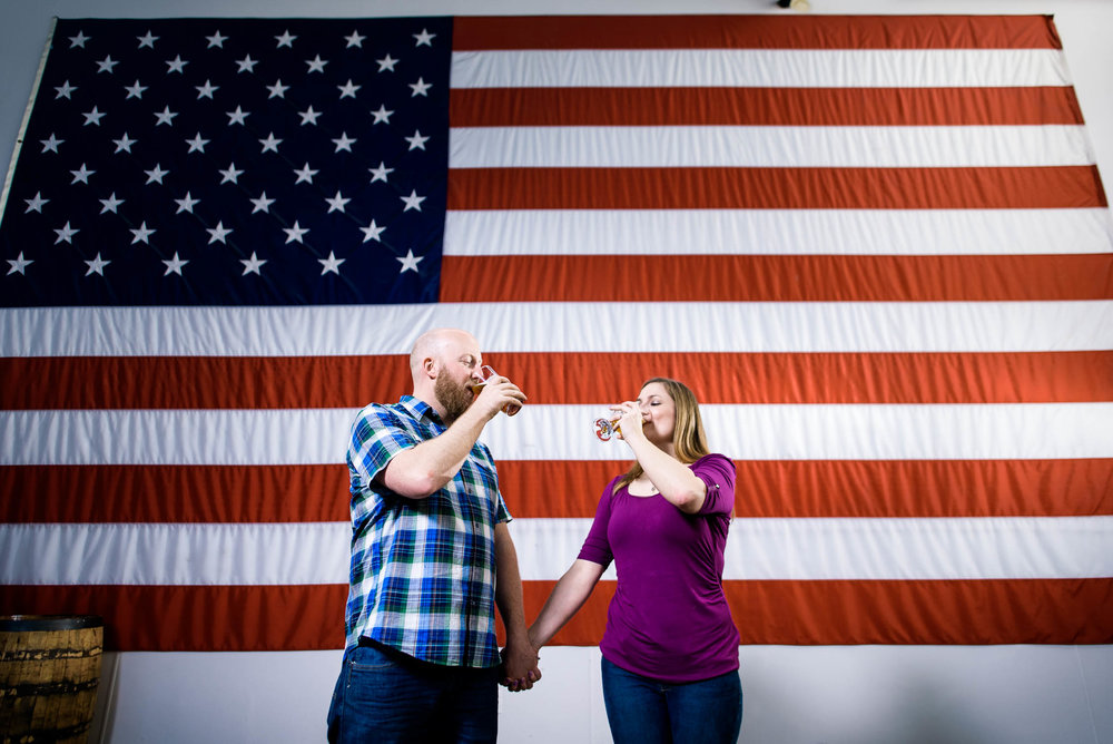 Couple shares a beer in front of the American flag at Revolution Brewing.