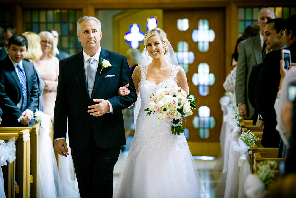 Father and bride walk down the aisle during a wedding at Baker Memorial United Methodist Church in St. Charles