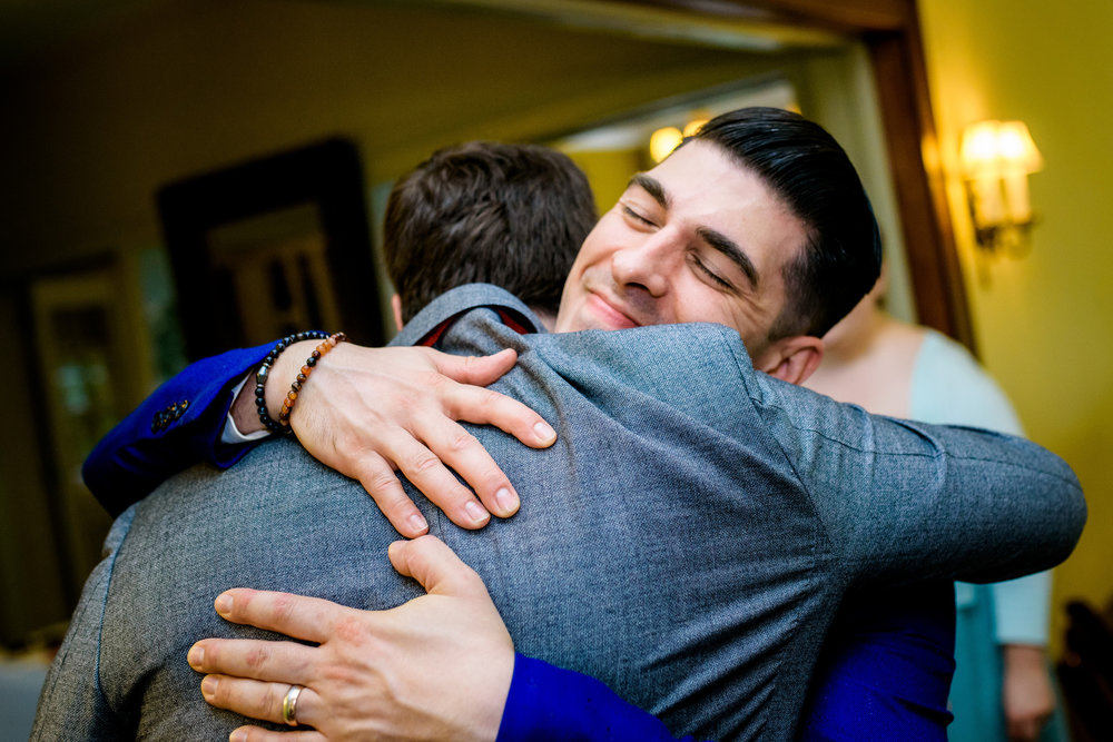 Groom gets a hug during a Cheney Mansion wedding in Oak Park.