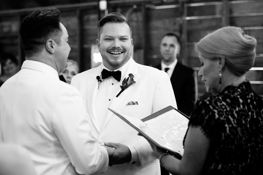 Grooms share a laugh during their wedding at Heritage Prairie Farm.