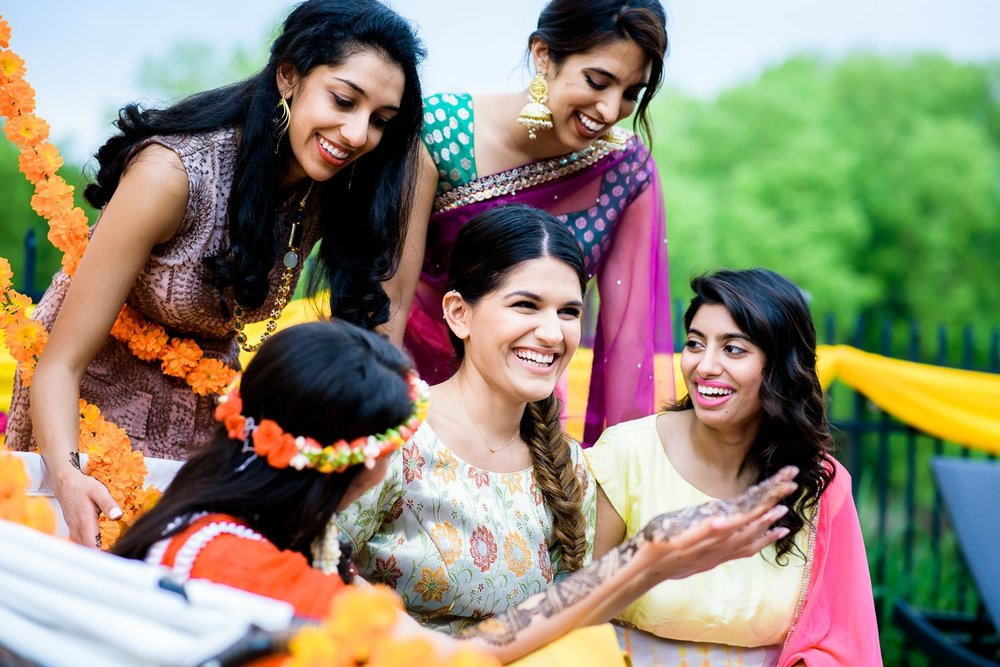 Bridesmaids with the bride while her henna is done during an Indian wedding mehndi in South Barrington, Illinois.
