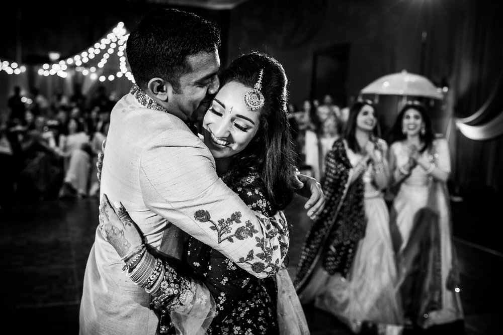 Bride and groom embrace during an Indian wedding sangeet at Stonegate Banquets in Hoffman Estates.