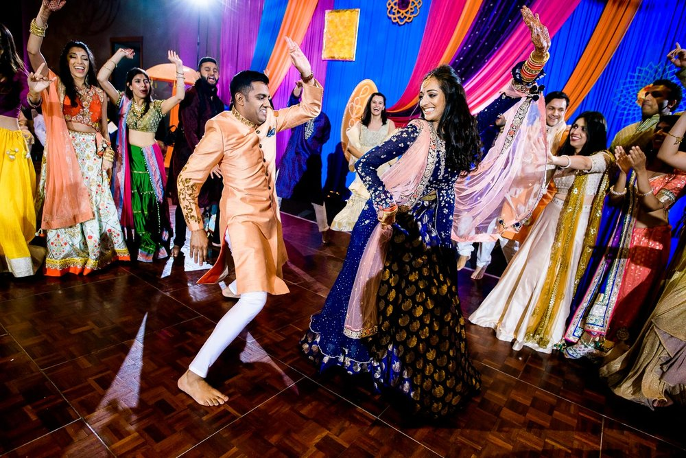 Couple and wedding party dance during an Indian wedding sangeet at Stonegate Banquets in Hoffman Estates.