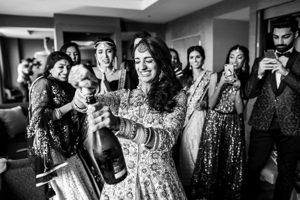 Brides pops the champagne during her Renaissance Schaumburg Convention Center Indian wedding.