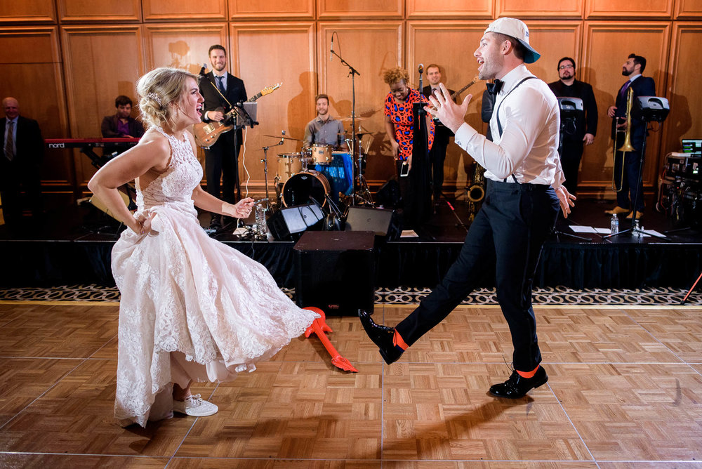 Bride and brother dance during a wedding reception at the Mid America Club in Chicago.