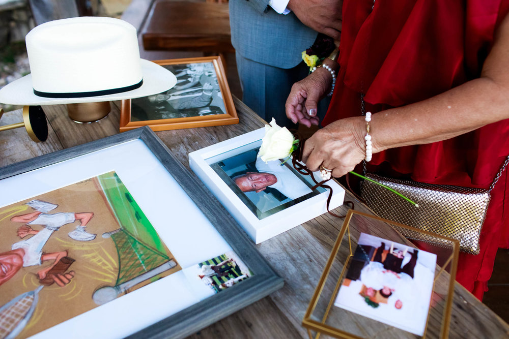 Mother of the groom rests a flower on a photo of her husband during a Montesino Ranch wedding Austin, Texas.