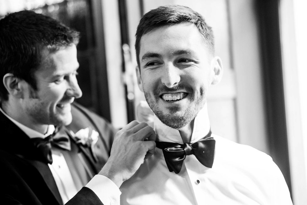 Best man helps the groom with his tie during a Blackstone Chicago wedding.
