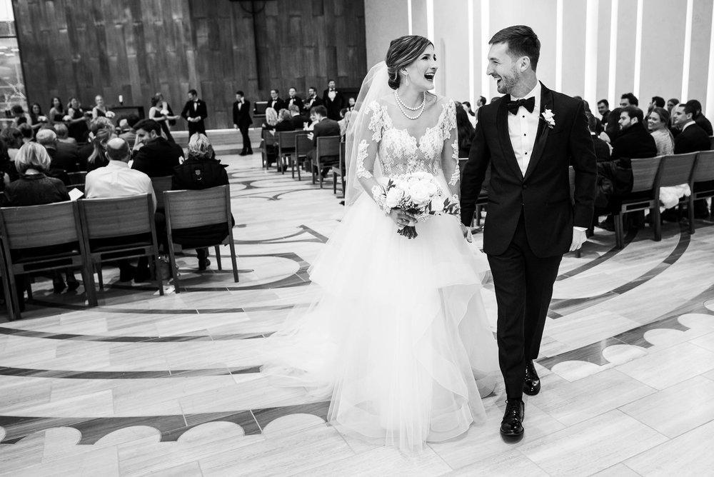 Bride and groom laugh while walking down the aisle during a Fourth Presbyterian Church wedding.