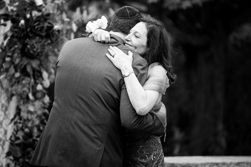 Mother and groom hug during an Independence Grove Chicago wedding.
