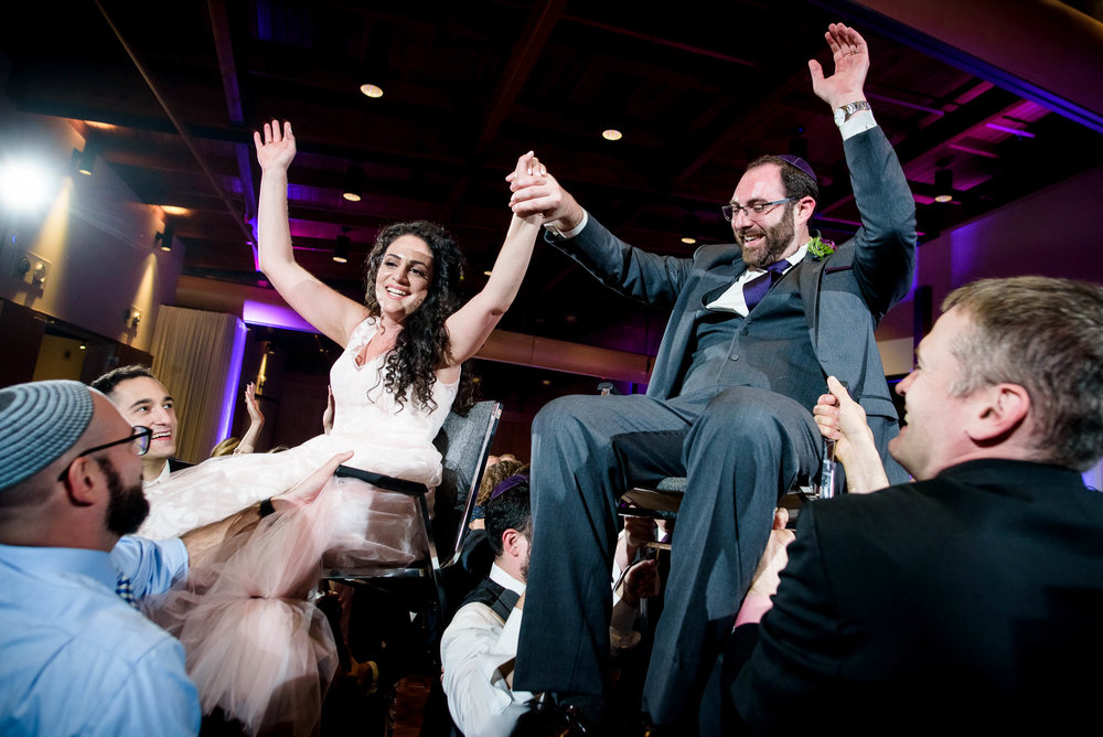 Bride and groom up on chairs during the horah during an Independence Grove Chicago wedding.