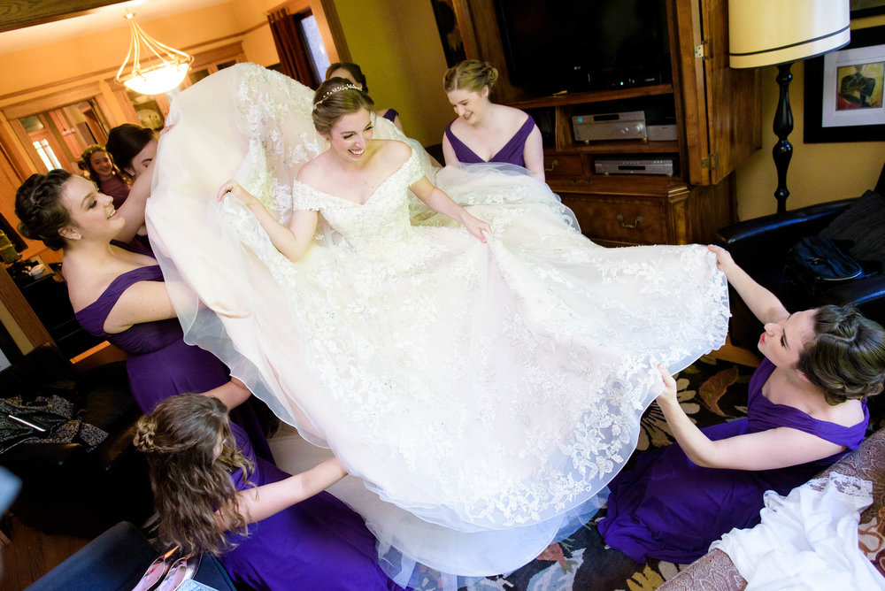 Bridesmaids help the bride with her dress during a Newberry Library Chicago wedding.