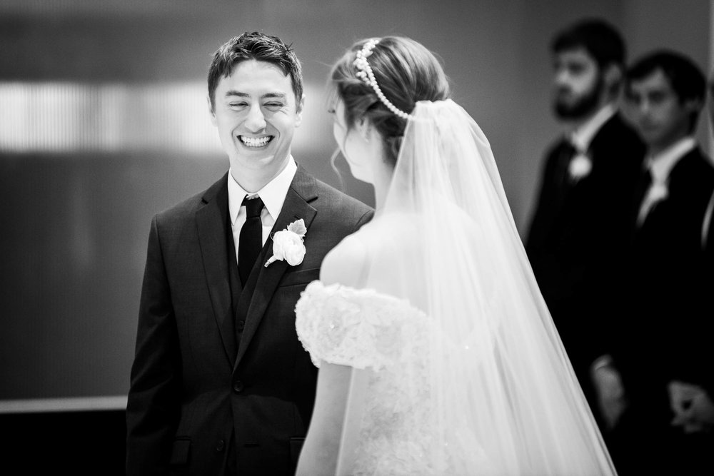 Groom laughs with the bride during a wedding ceremony at Madonna Della Strada.