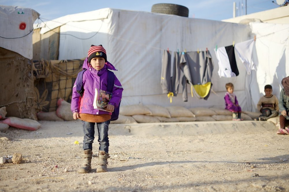 A refugee from Homs, Syria living in a tent settlement camp in the Bekaa Valley near the Syrian border wearing warm clothing distributed by Sadalsuud.