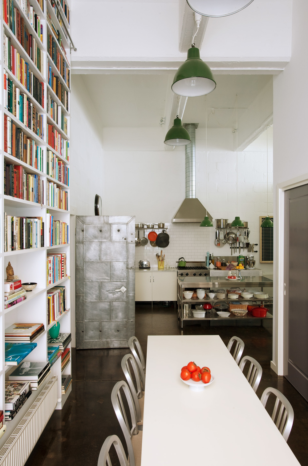 casual-dining-industrial-kitchen-green-overhead-pendants-floor-to-ceiling-bookshelf-diane-bergeron.jpg