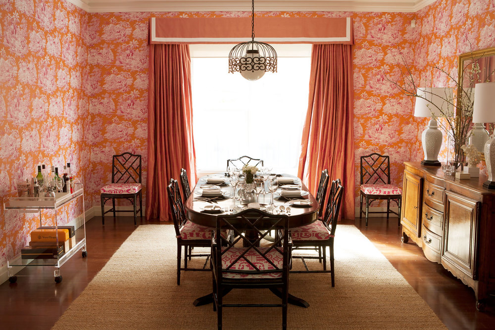 orange-pink-toile-wallpaper-vintage-white-table-lamp-black-lacquer-dning-table-faux-bamboo-chair-gold-mirror-natural-rug-pendant-pink-window-dressing-pelmet-walnut-floorboard-diane-bergeron.jpg