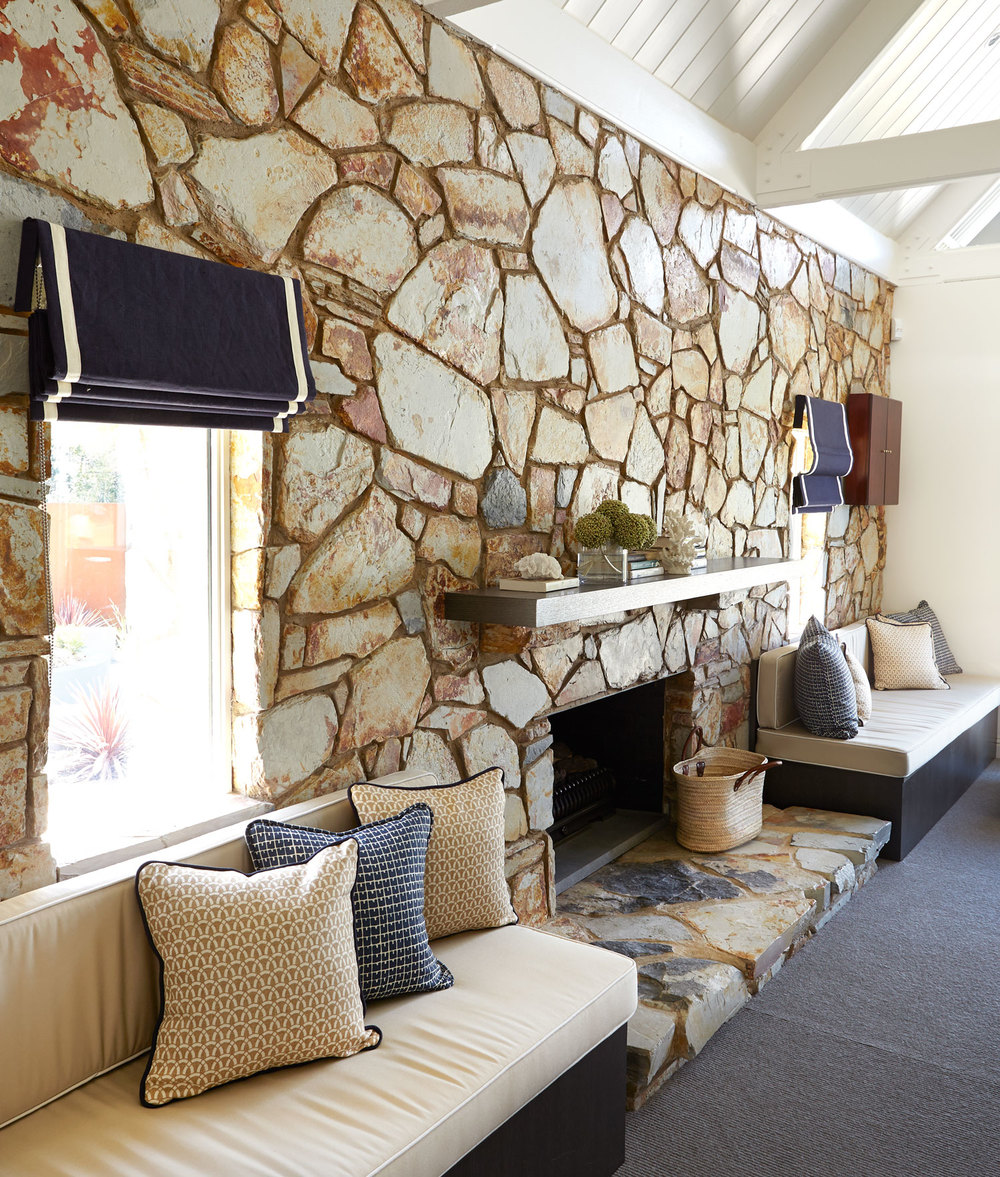 stone-wall-leisure-room-navy-white-roman-blind-upholstered-window-seat-printed-cushion-fireplace-basket-charcoal-diane-bergeron.jpg