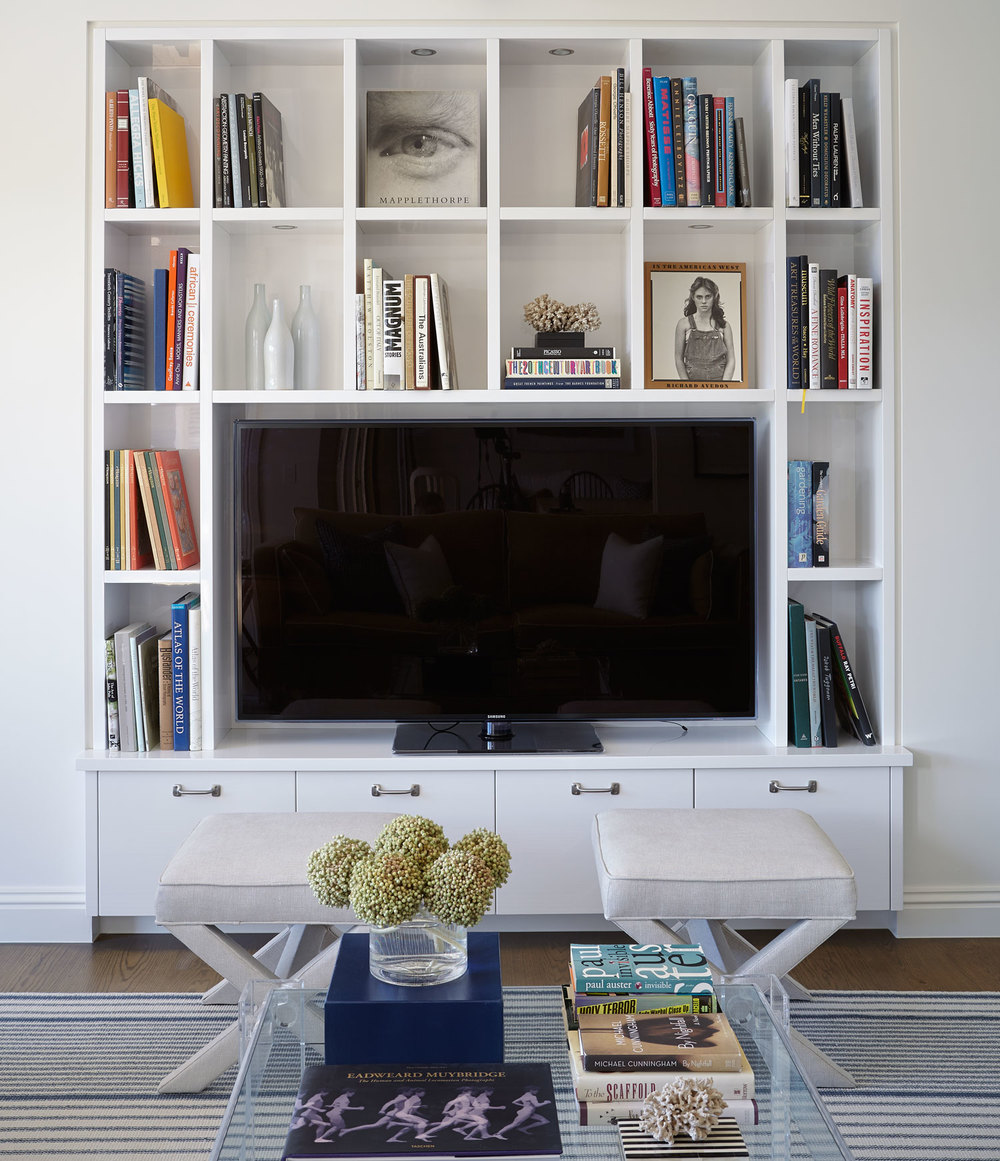 cross-base-upholstered-foot-stool-glass-coffee-table-custom-entertainment-unit-white-finish-stripe-rug-diane-bergeron.jpg