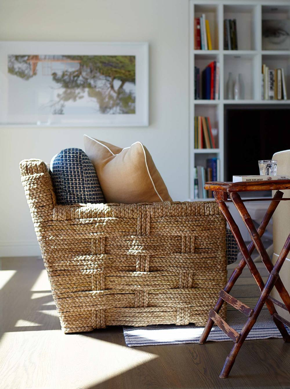 beach-house-living-room-wicker-caned-armchair-patterned-cushions-stripe-rug-neutral-sisal-palette-custom-joinery-white-lacquer-bookshelves-tv-unit-bamboo-butlers-tray-table-diane-bergeron.jpg