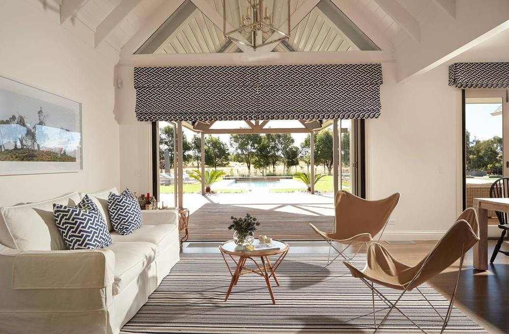 beach-house-living-room-white-linen-slipcovered-sofa-nickel-pendant-blue-roman-blinds-patterned-cushions-stripe-rug-neutral-sisal-palette-white-walls-diane-bergeron.jpg