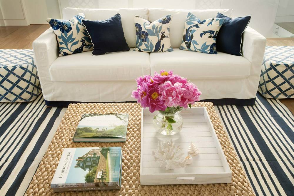beach-house-living-room-white-linen-slipcover-sofa-navy-cushion-floral-cushion-cane-coffee-table-stripe-rug-white-lacquer-tray-diane-bergeron.jpg