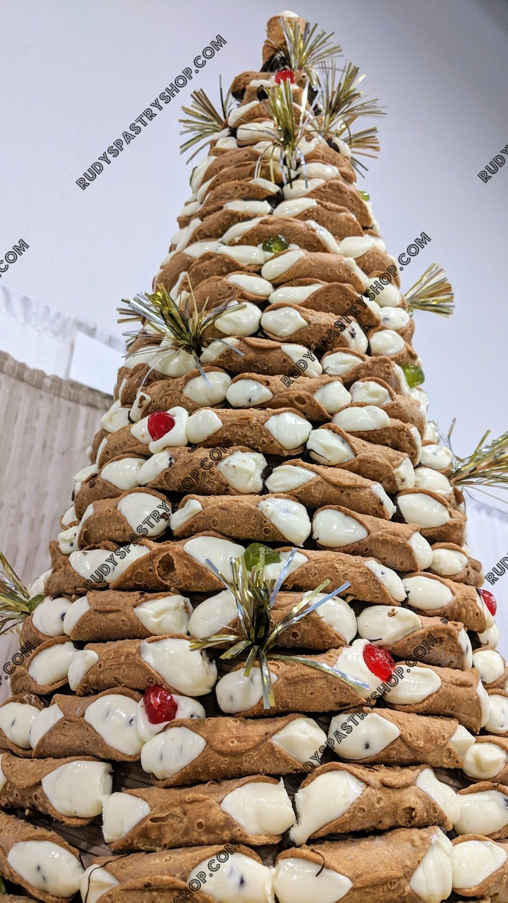 Holy Cannoli Tree - At Rudy's Pastry Shop we want to offer something special and over the top for our customers. Feast your eyes on our 4 Foot Holy Cannoli Tree cake. This delicious beauty will make a wonderful center piece or addition to any event you are hosting.This cake can be a fantastic, delicious, and fun focal point for your Wedding, Birthday party, Fundraiser, Company Event, or any Celebration.If this is a bit larger than you may need, we do offer alternate sizes in a 3, 2, or 1 Foot Cannoli Tree cake.Call to order your Cannoli Tree today! 973.743.3768