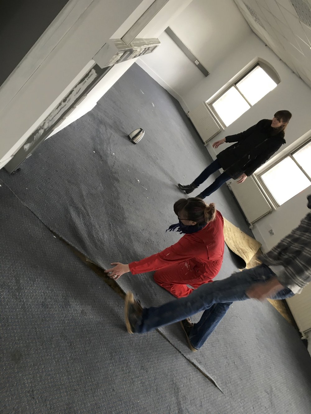 Gemma, David, Elizabeth and more start to take up the old carpet in the rehearsal room