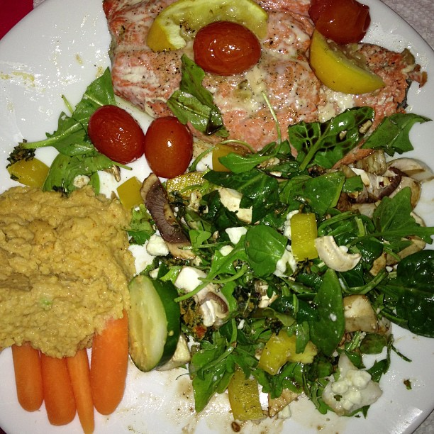 Salmon, spinach salad and homemade hummus Roast cherry tomatoes in olive oil, salt, fresh minced garlic, pepper for 15min at 375 degrees. Put in salmon and mix dressing on top along with lemon juice. Cook another 10min. Serve with fresh greens and veggies with citrus dressing (lemon juice, pepper and olive oil) and homemade garlic hummus.