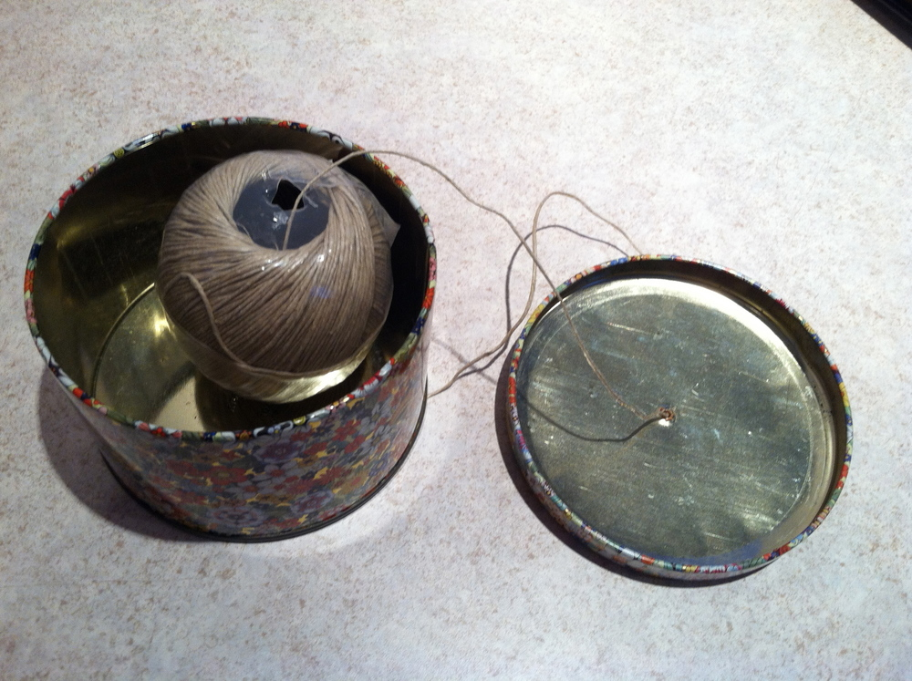 I took a simple tin (purchased for $0.50 at Agape) and punched a hole in the lid. The ball of twine fits perfectly.