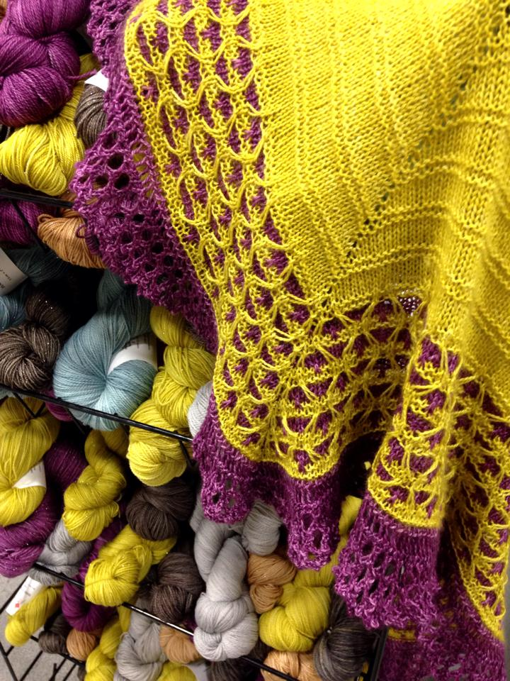 Our colorways from January's TNNA - the shawl is in Temperance and Prudence, and on the rack you can see Gravity, Nimbus, Penny, and Sexy.