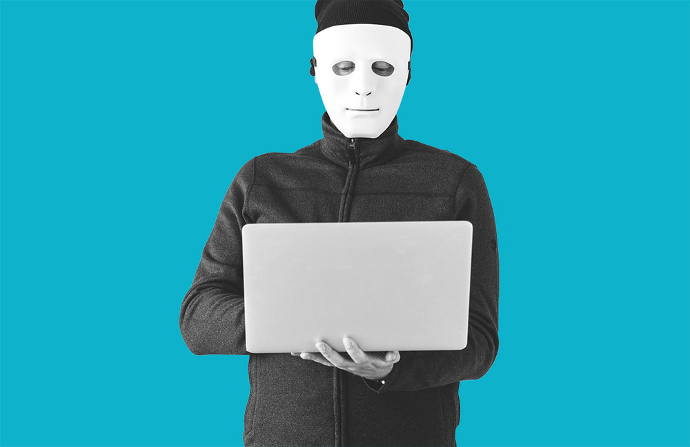 Image of masked person holding a laptop computer. Credit: Rawpixel (via Unsplash)