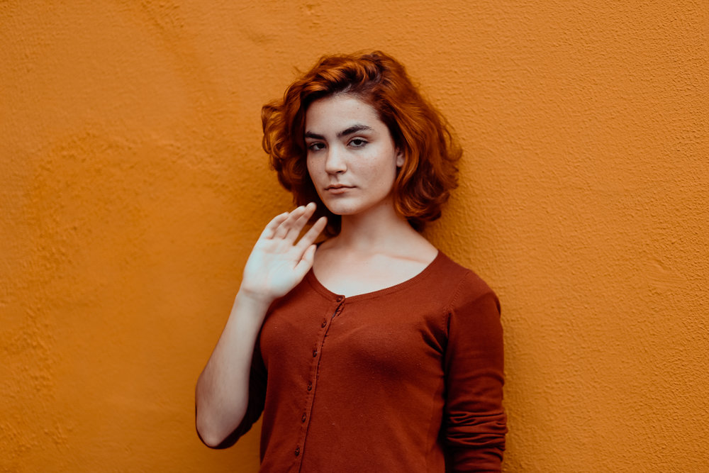 Image of unsmiling person with shoulder-length red hair standing next to an orange wall, via Unsplash