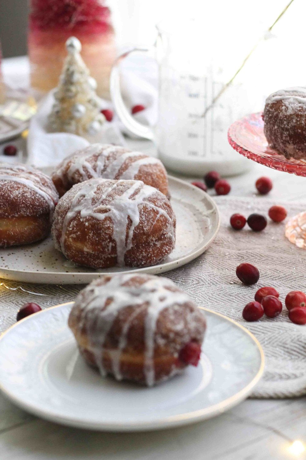 Soft, orange-scented doughnuts are rolled in cinnamon sugar and stuffed with homemade cranberry jelly before being drizzled with vanilla bean glaze.  The perfect Christmas morning treat.  {Pedantic Foodie}