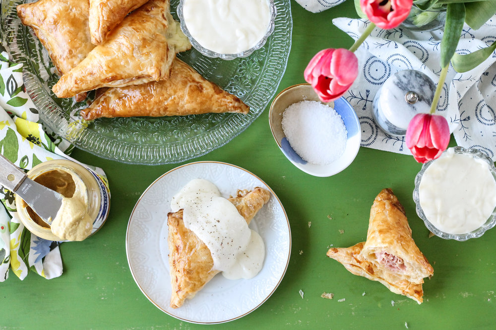 These mini hand pies are a fresh, easy-to-eat take on the classic Croque Monsieur.  Havarti & Ham Hand Pies are served with a rich, Gruyere Bechamel.  Find the super simple recipe on WWW.PEDANTICFOODIE.COM!