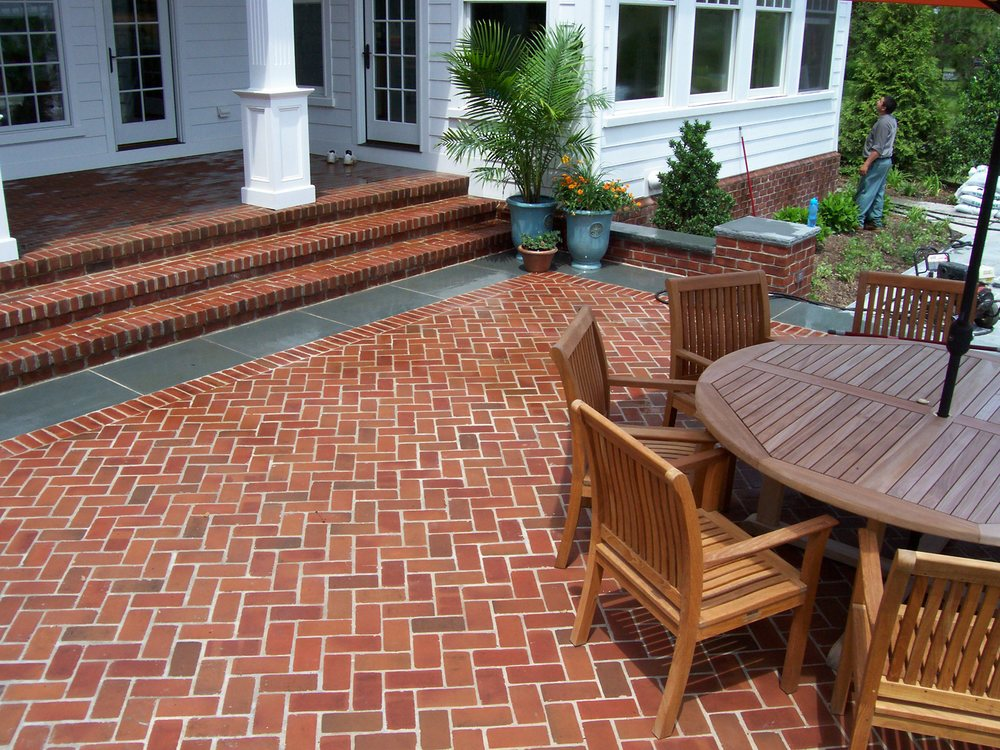 Brick pavers in a herringbone pattern set with a flamed bluestone border.