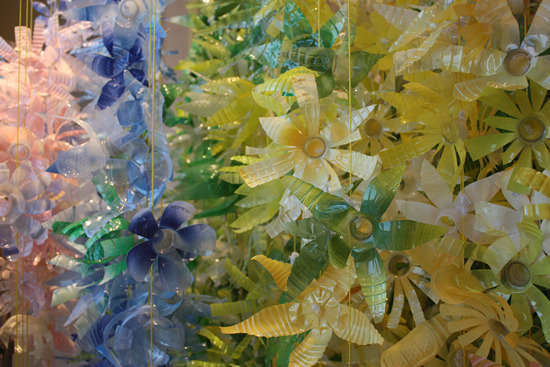 My intern and I made almost 2000 of these flowers—out of plastic  bottles! We collected bottles from employees and a local gym and cut the  tops and bottoms into petals. I then spray painted the back of the  flowers to give them color but still keep that shiny lustre.